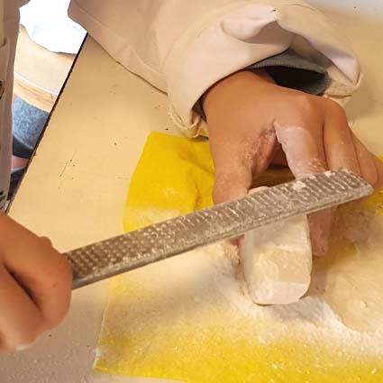 Handen die met een grote vijl een stuk speksteen bewerken