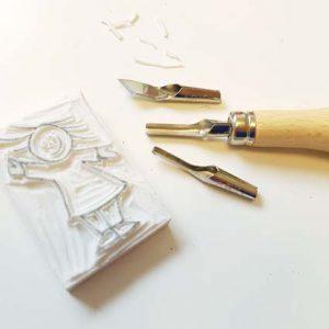 Een uit gum gesneden stempel van een poppetje, daarbij een guts en wat losse mesjes