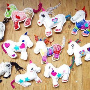 Verschillende door kinderen gemaakte unicornknuffels tijdens een kinderfeestje.