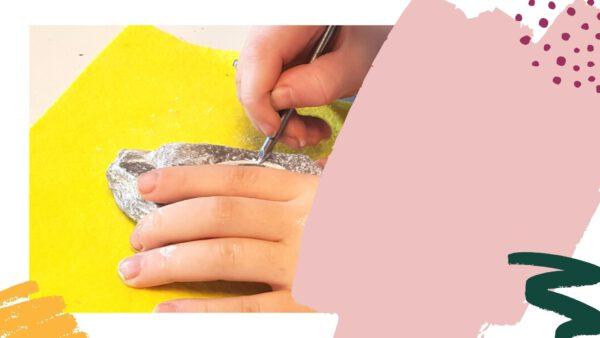 Handen die met een spijker details in een stuk speksteen krassen (deel van video)